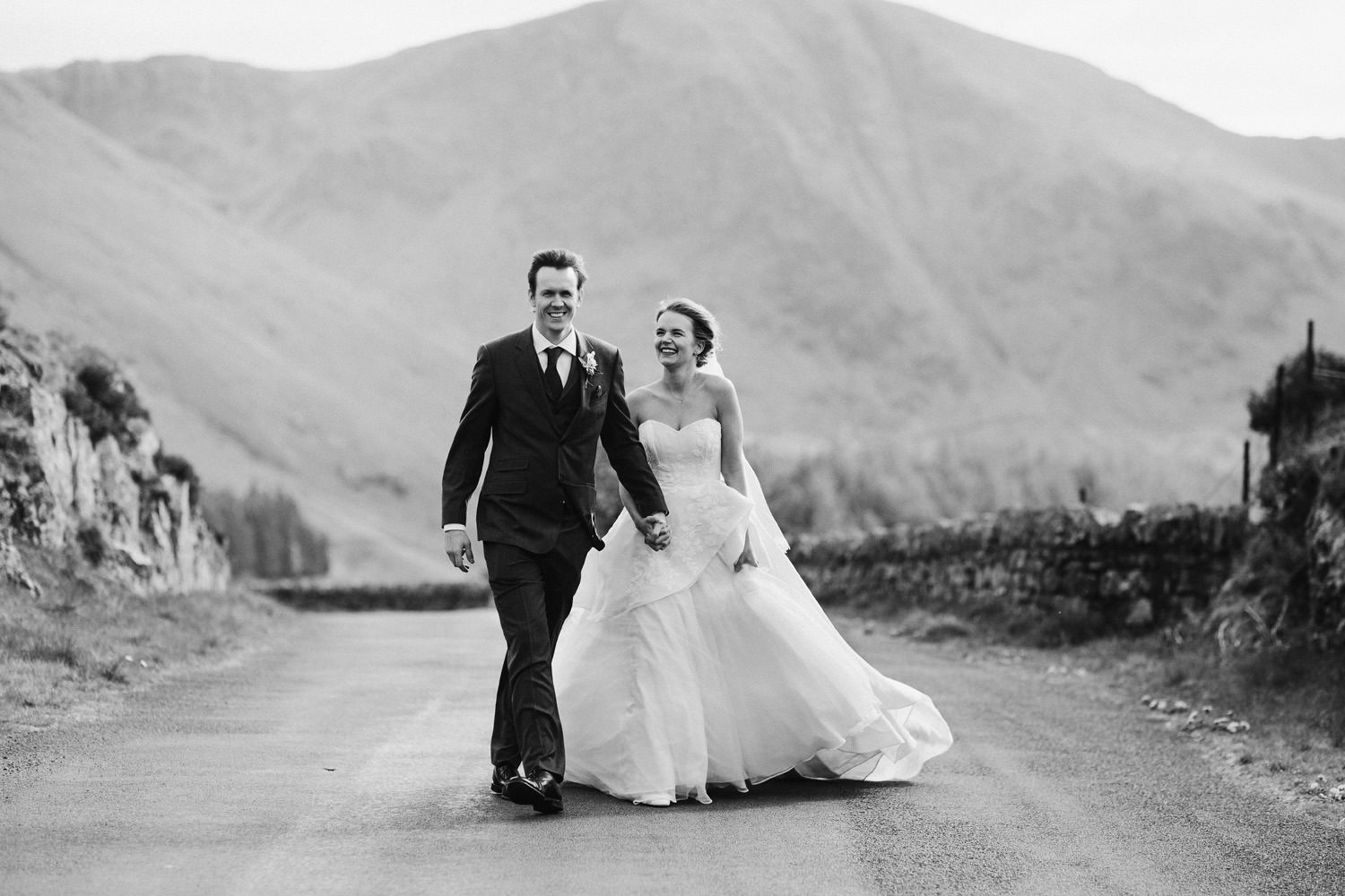 Bride and groom walking along a road in Cumbria