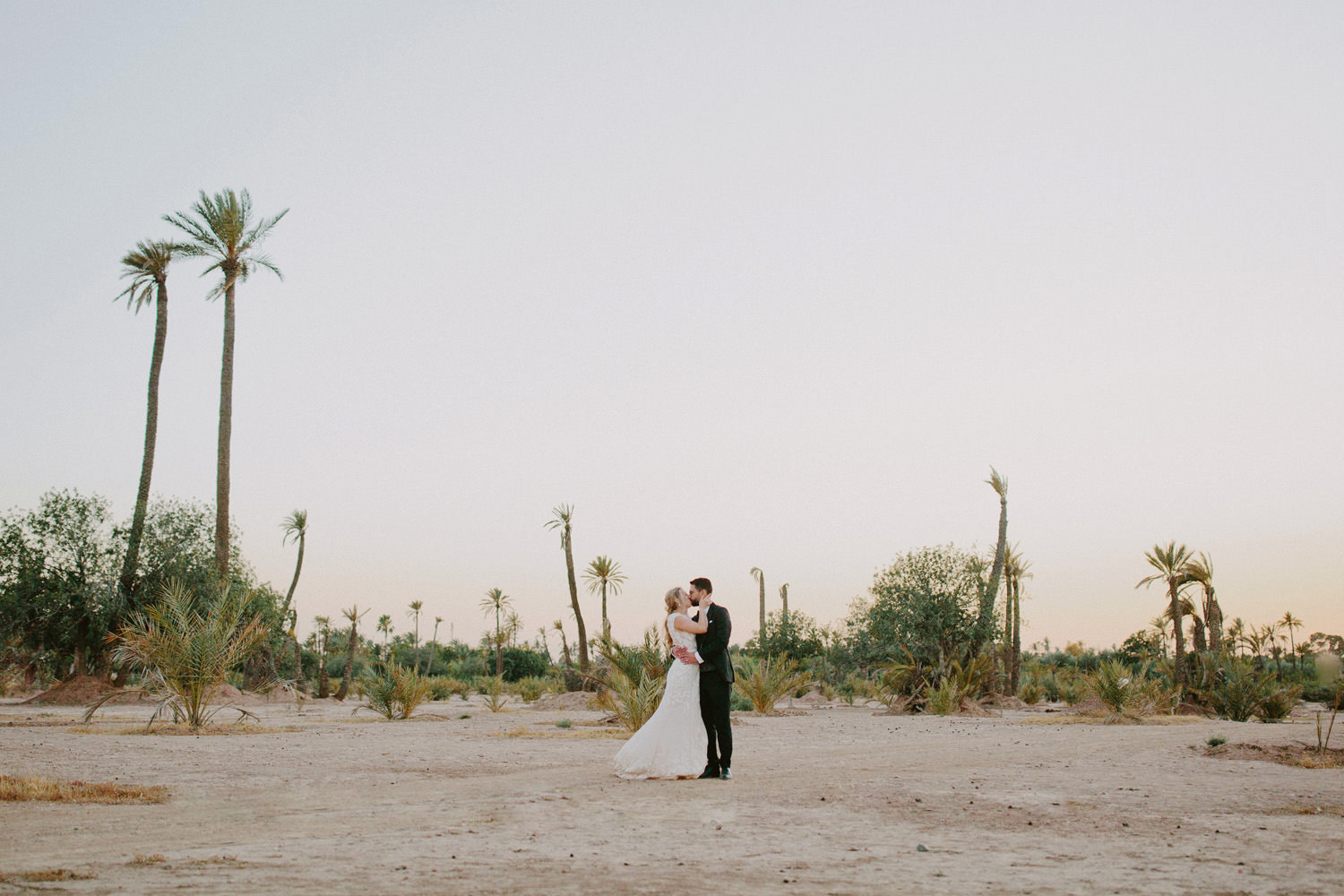 Bride and groom kiss in the Marrakech desert