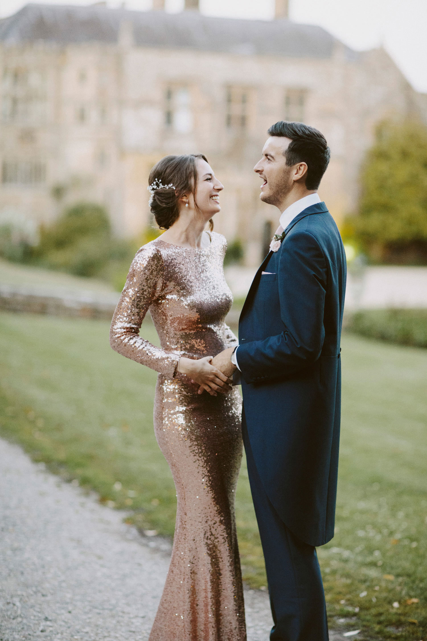 Bride in gold dress laughs with groom during Somerset wedding