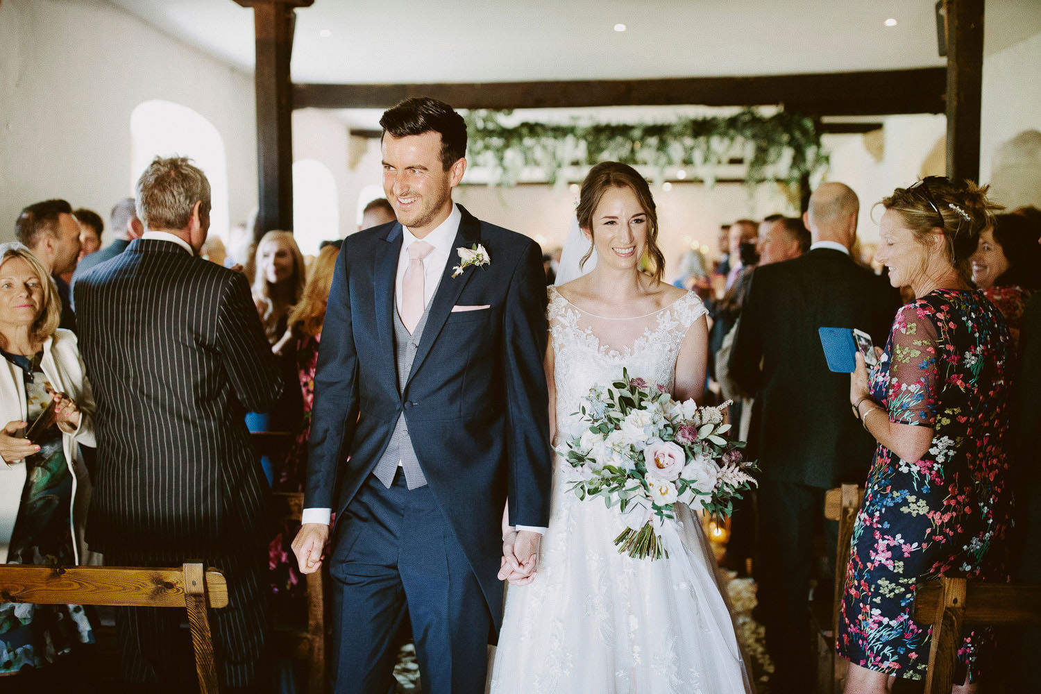 Wedding couple leave ceremony at Brympton House