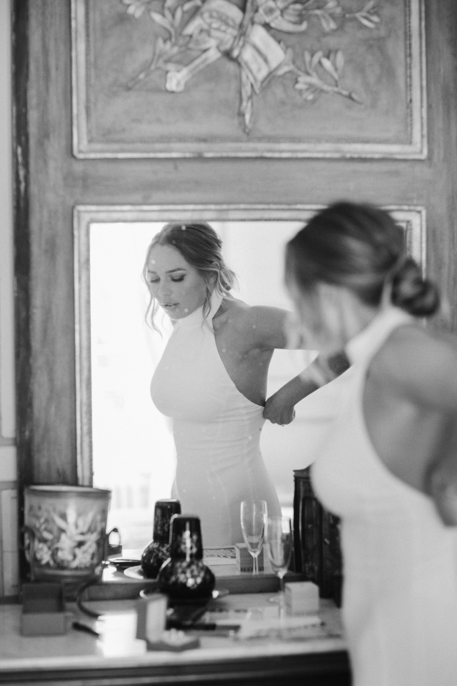 bride adjusting dress in mirror