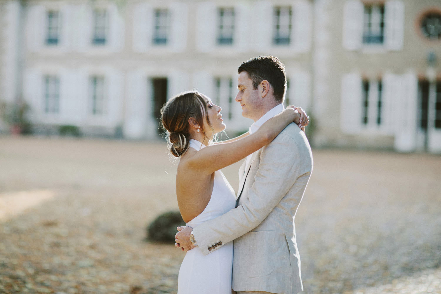 bride and groom hug in front of Chateau de Bouthonvilliers
