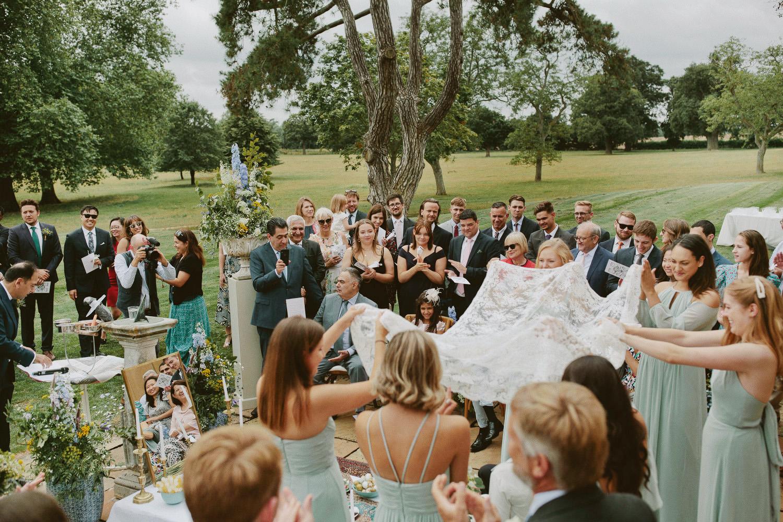 Wedding guests gather round outdoor Suffolk wedding ceremony