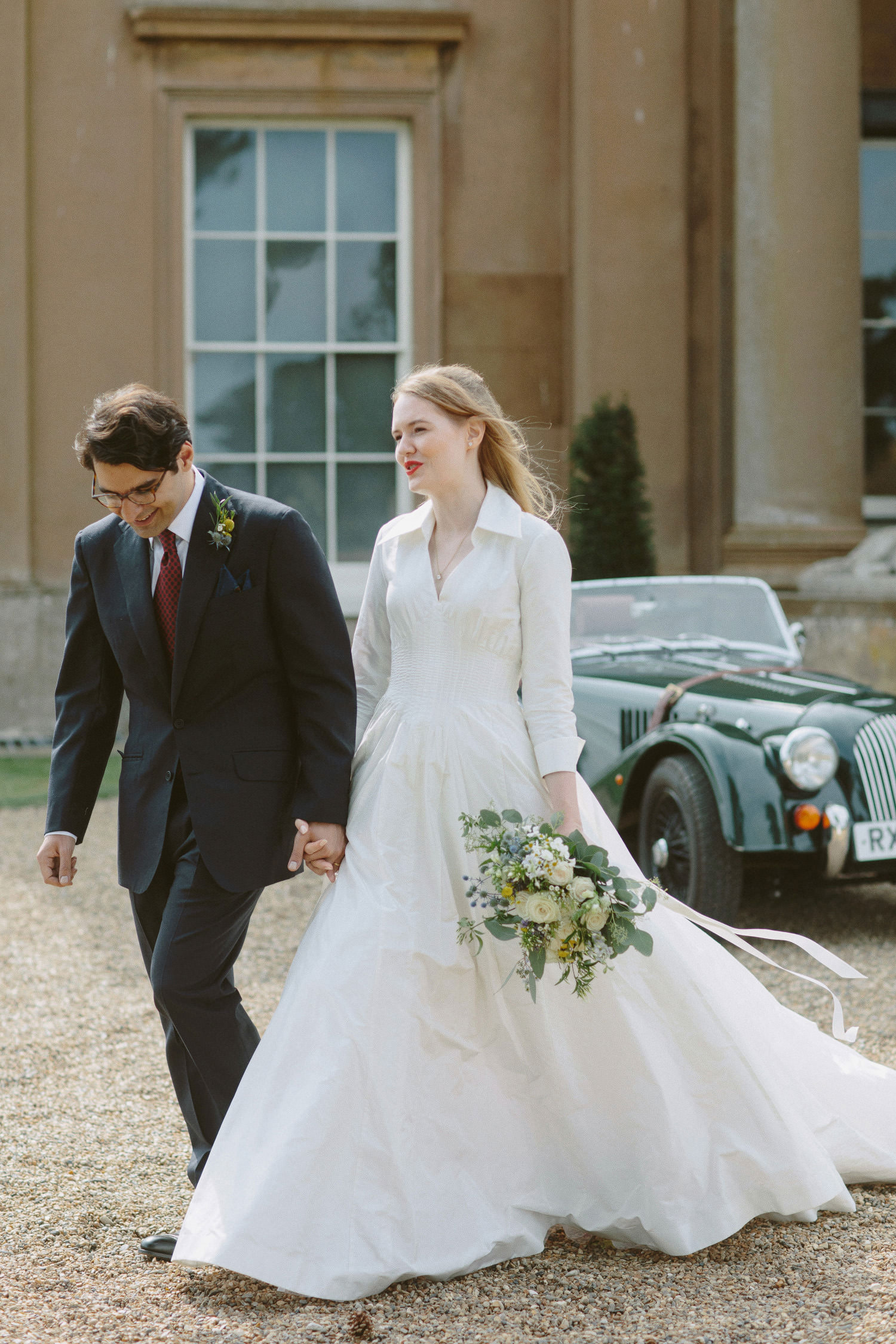 Bride and groom walk out from Suffolk wedding venue