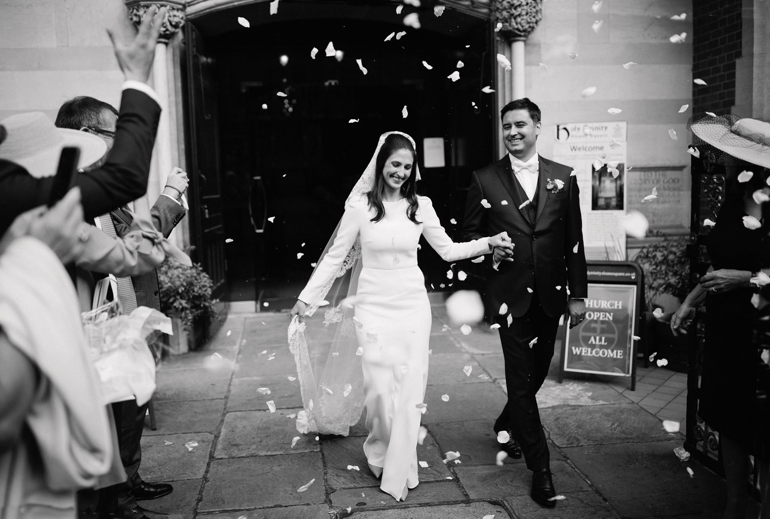 bride and groom walking out of Sloane street church with confetti in the air