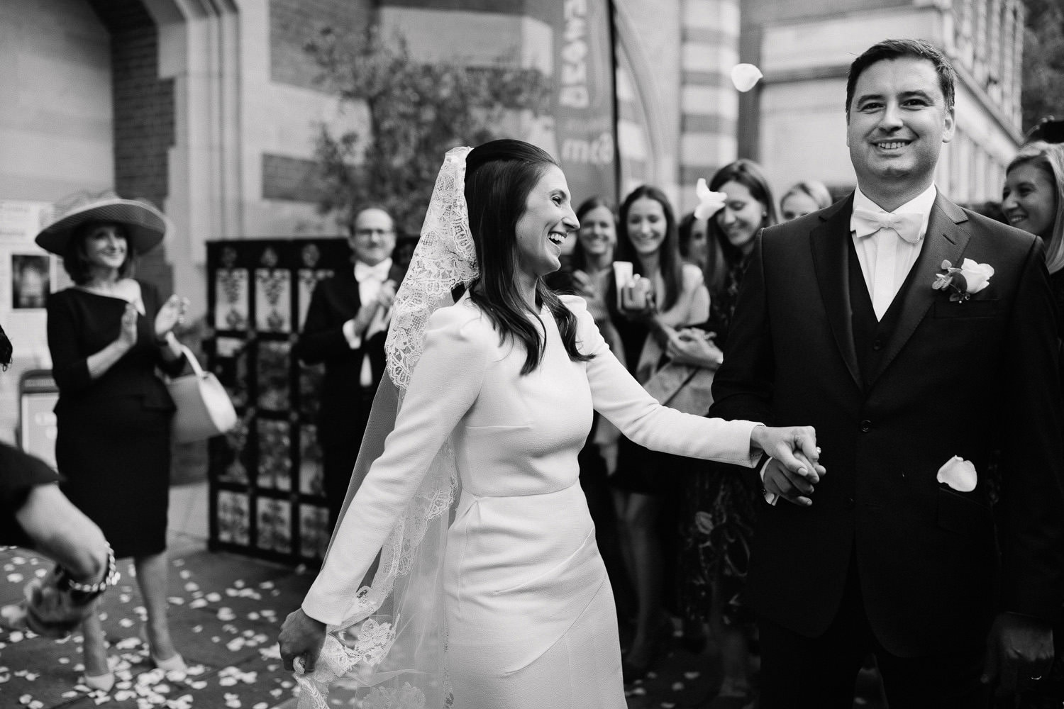 bride and groom smiling on the London street surrounded by friends
