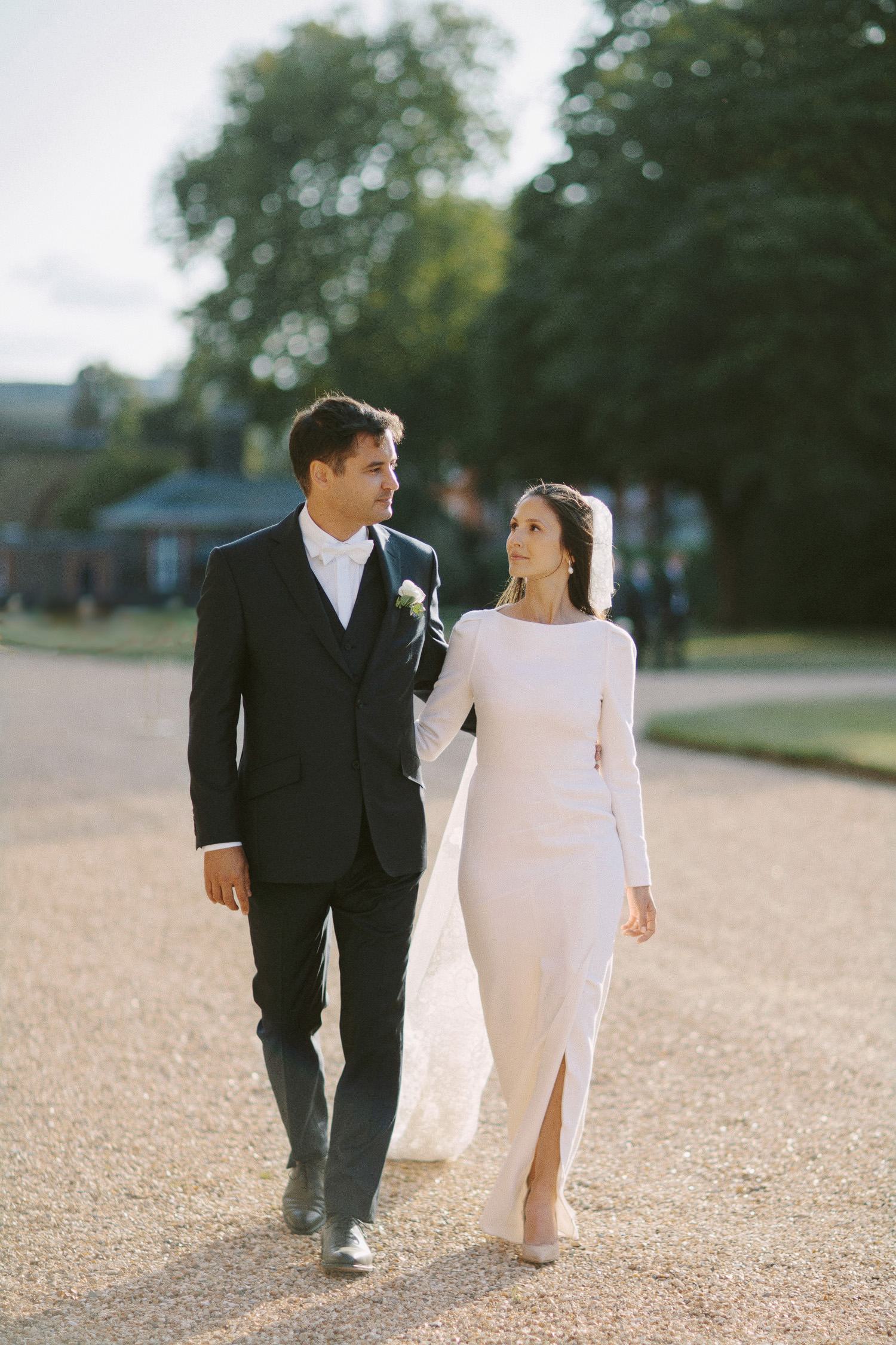 bride and groom walk in front of the Royal chelsea hospital