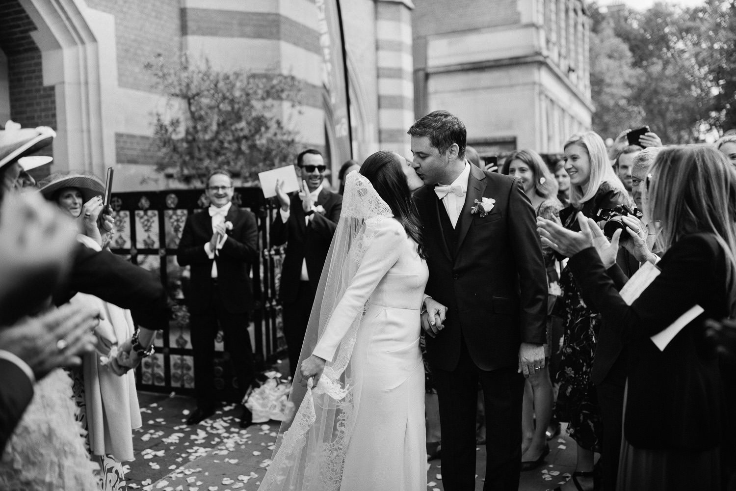 bride kisses groom with friends clapping on pavement in London