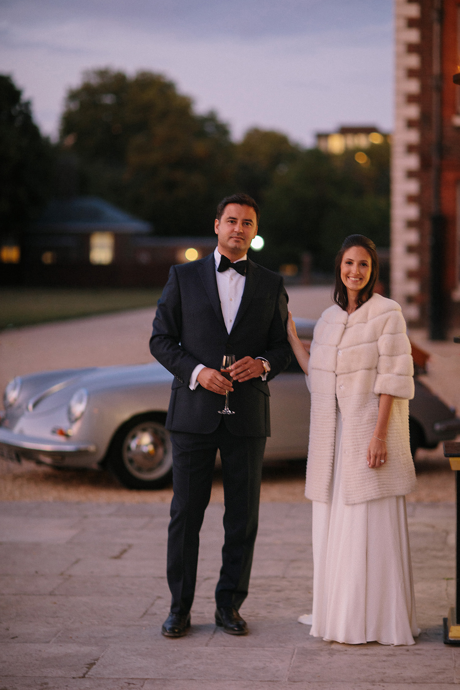 bride wearing warm white coat waits in evening light with groom