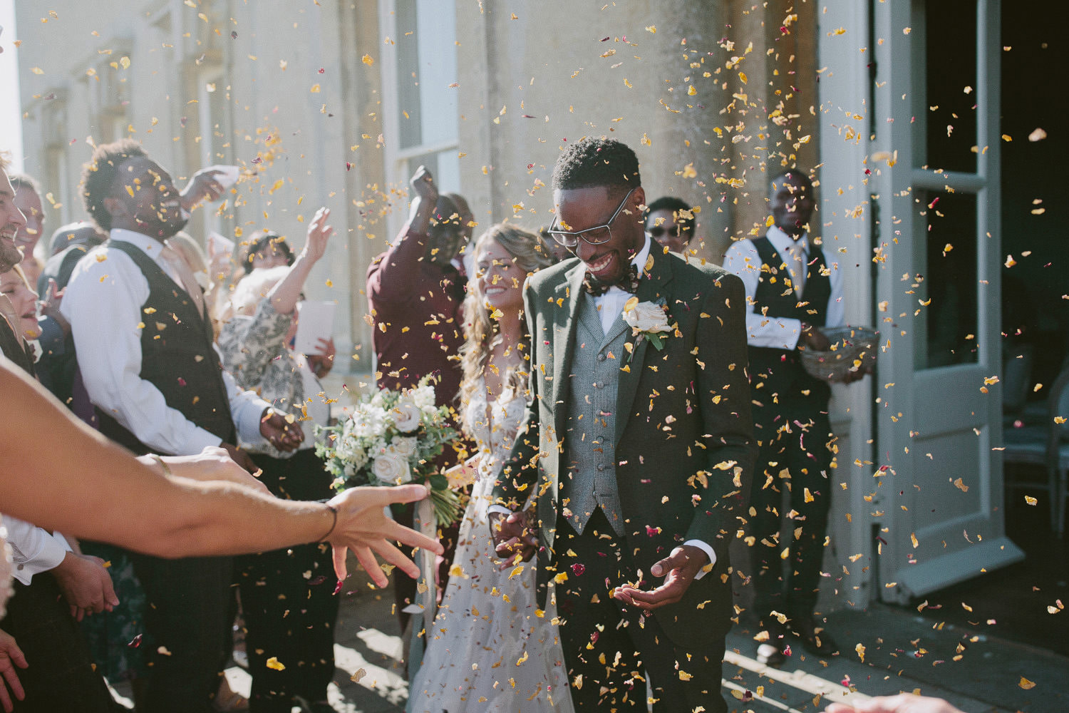 bride and groom walking out surrounded by guests throwing orange confetti