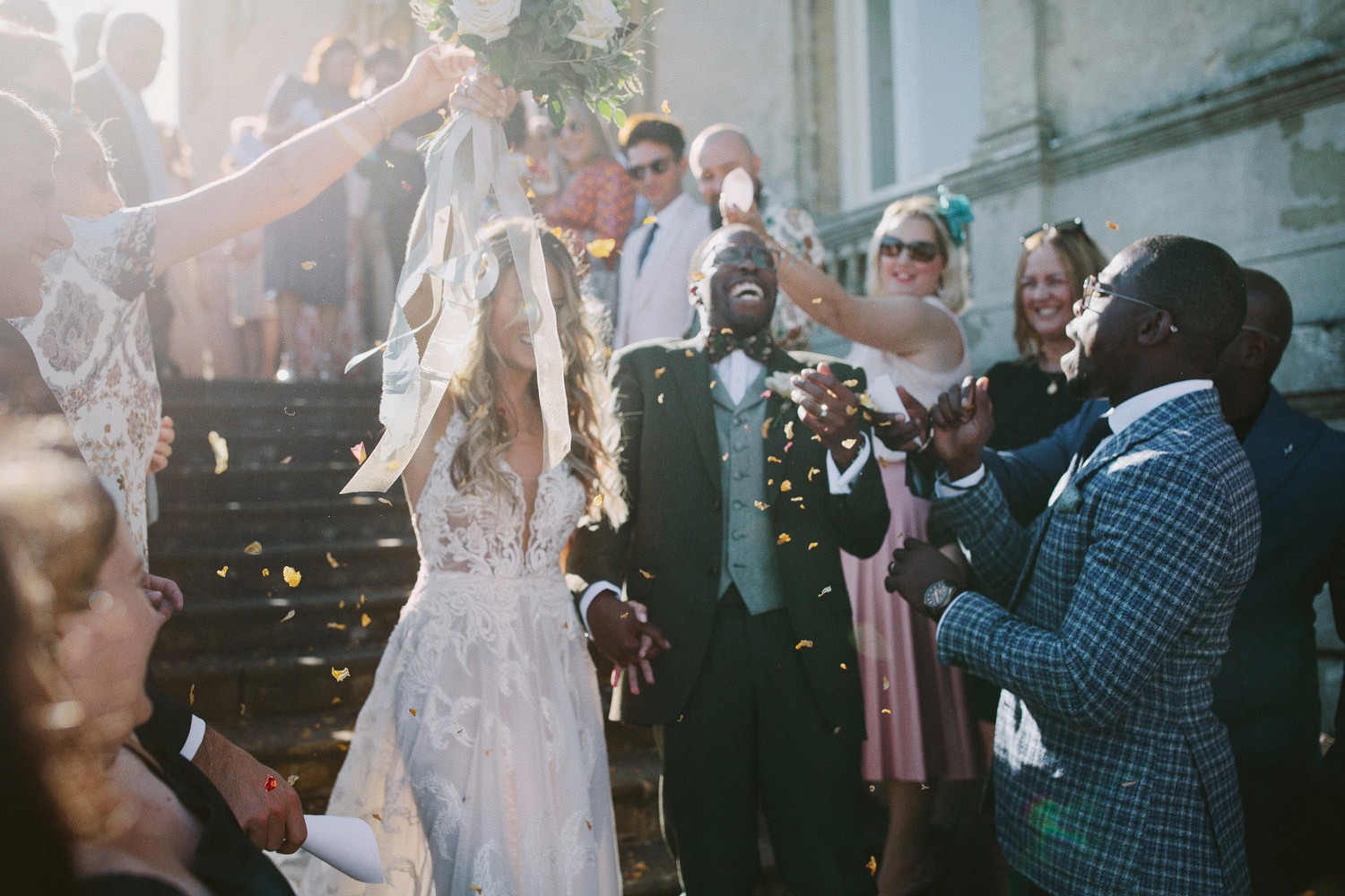 bride and groom walking down steps in sunlight with friends clapping