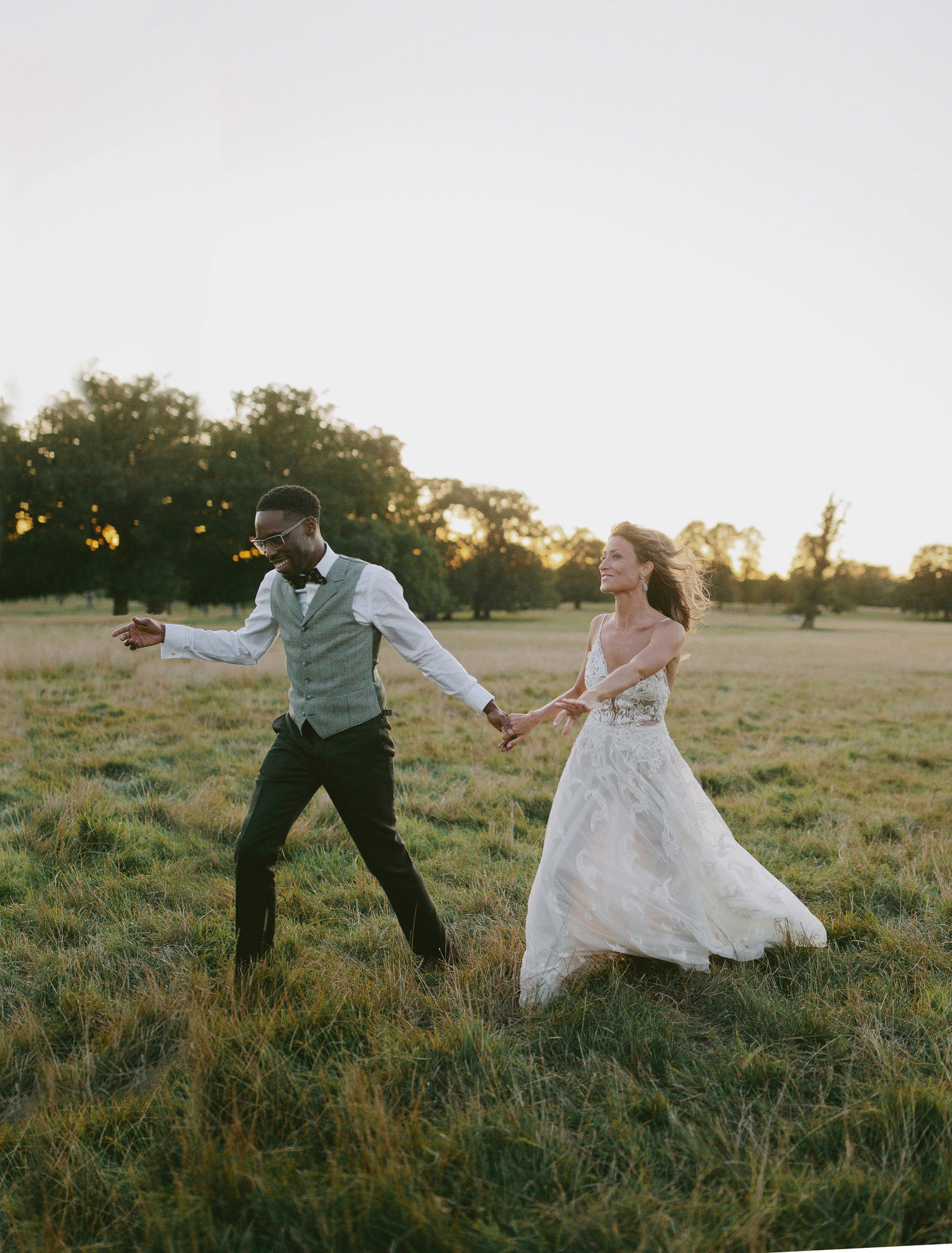 groom in bow tie leads bride in Liz Martinez dress through fields in front of Kirtlington park