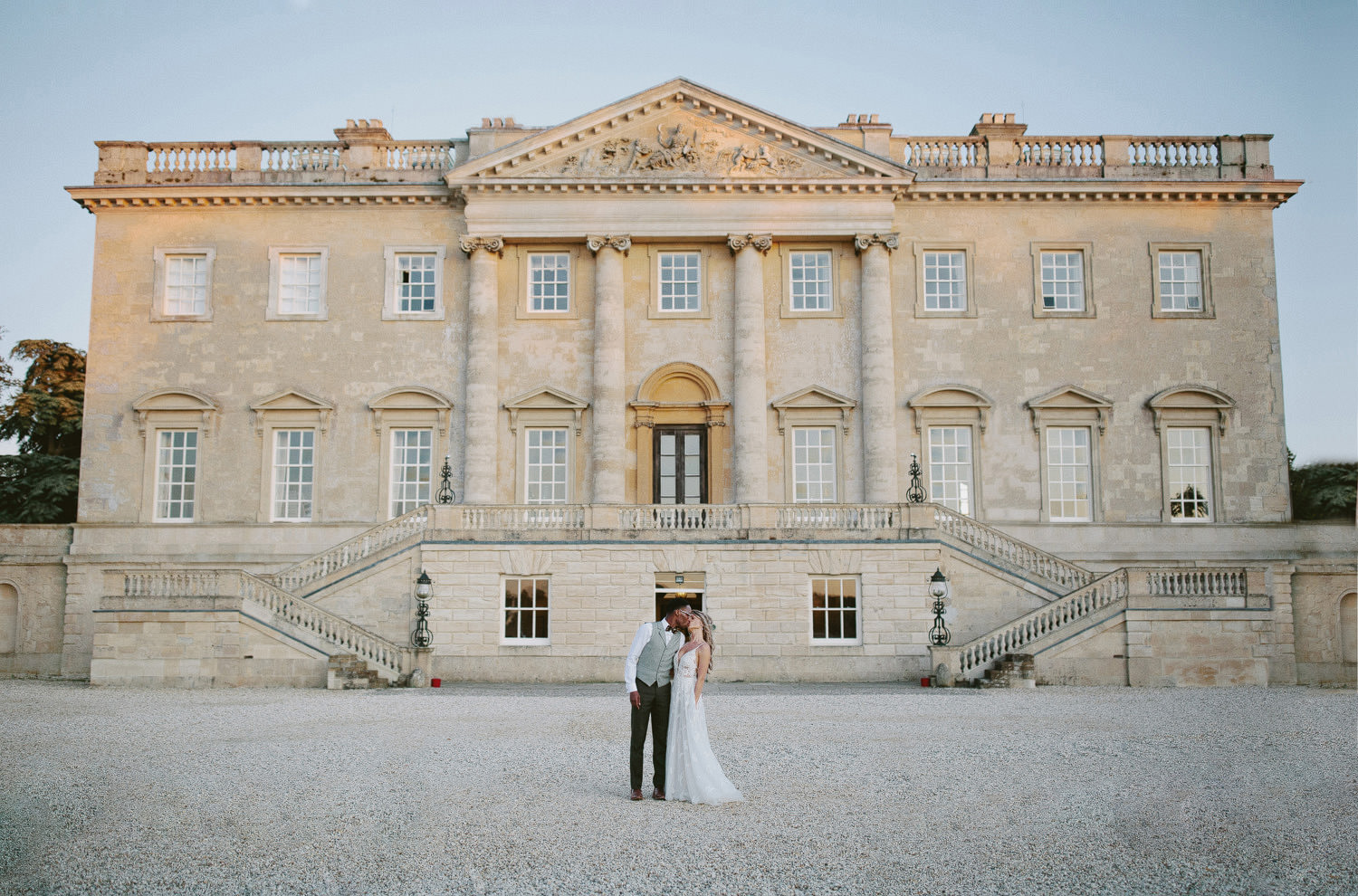 bride and groom kiss in front of Kirtlington park in Oxfordshire