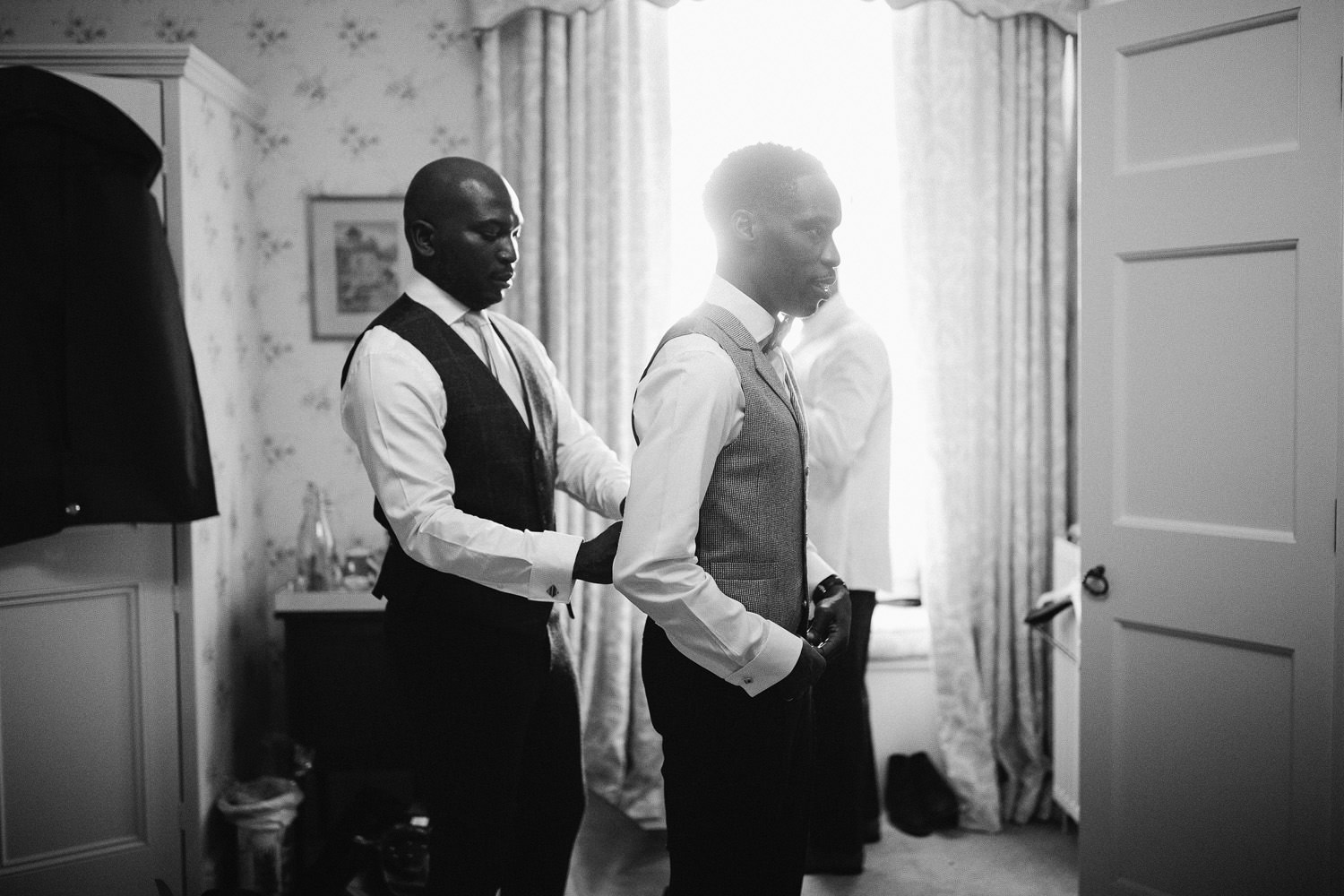 An usher ties up the back of a grooms waistcoat in a large bedroom