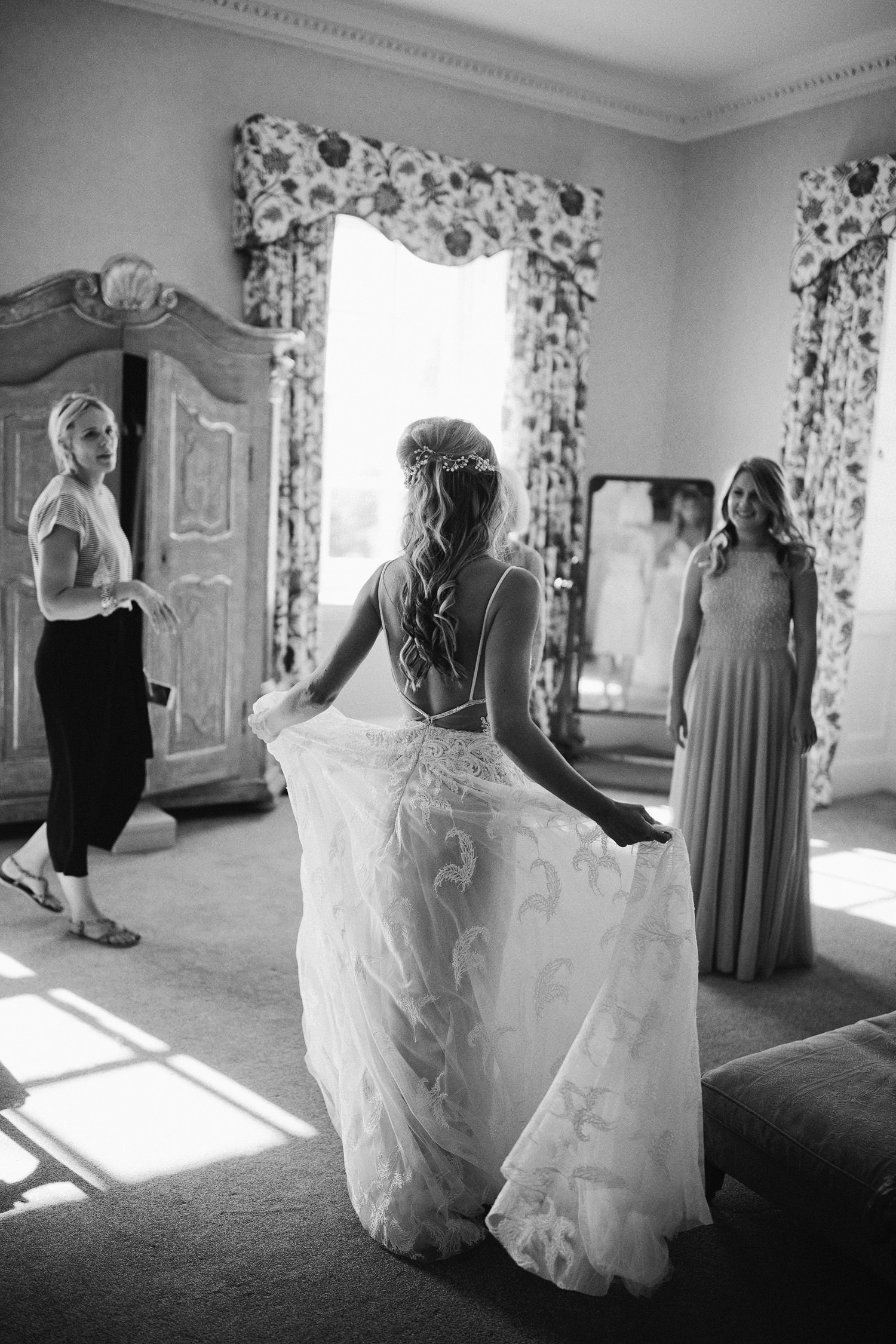 bride holds out her wedding dress to bridesmaid