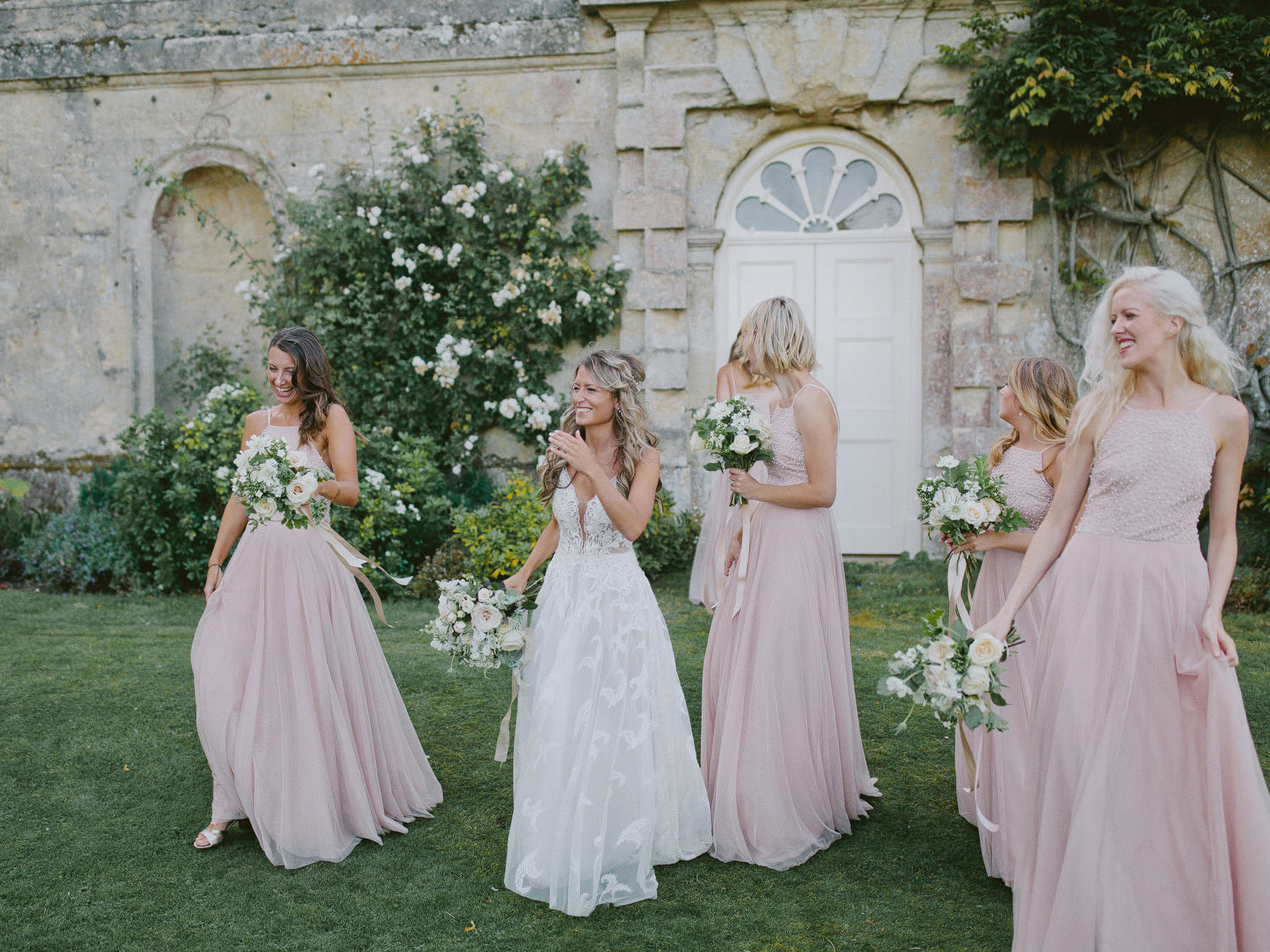 bridesmaid in blush pink dress walking with bride next to garden wall