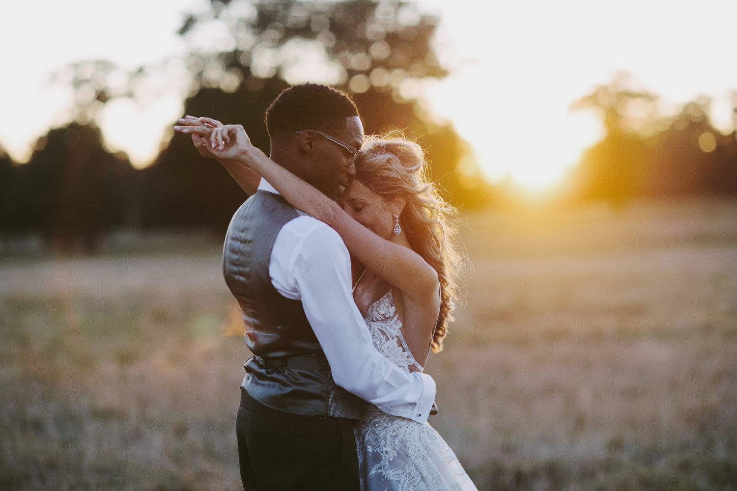 bride puts arms around groom in sunset at Kirtlington park