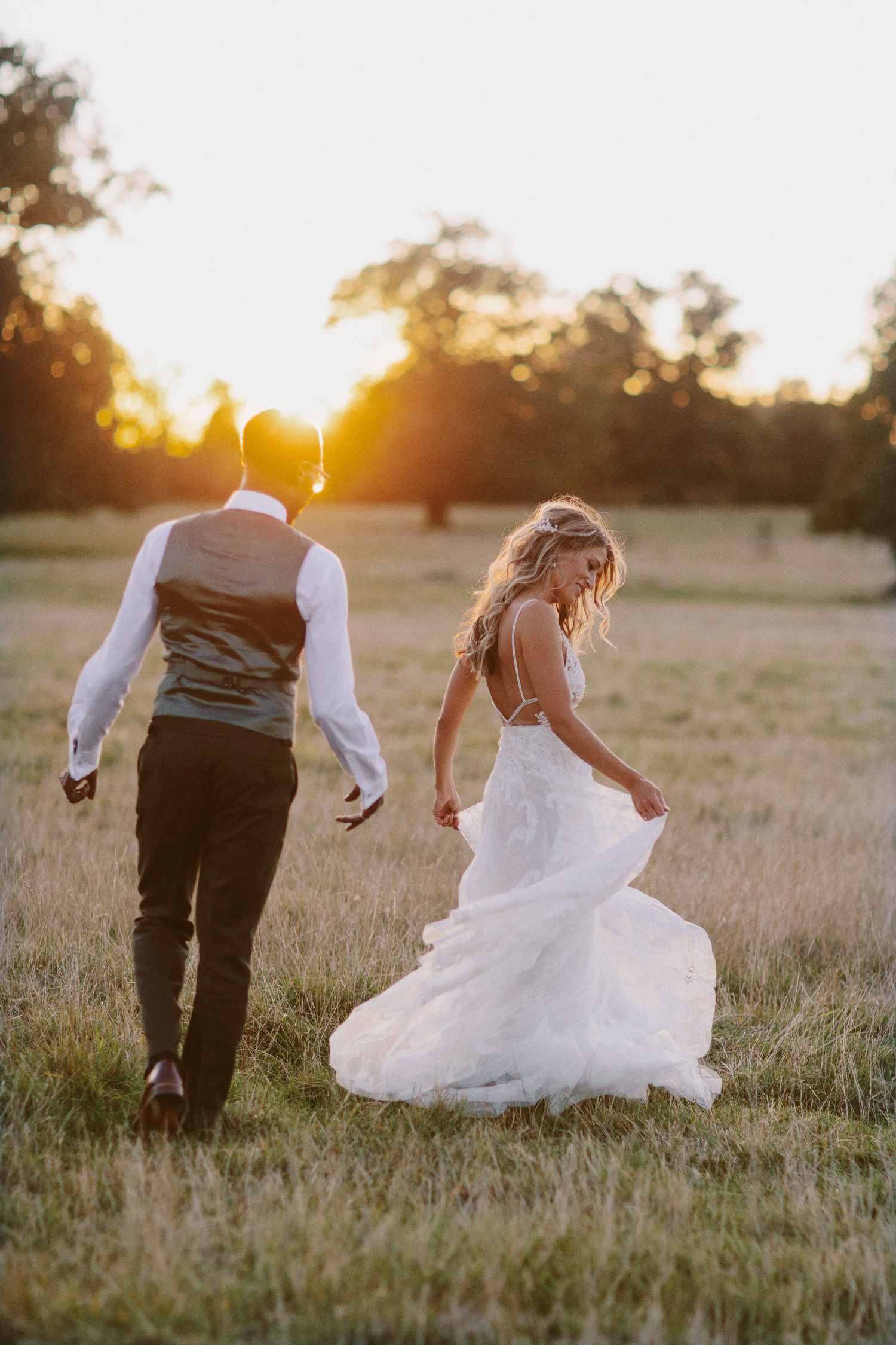 bride and groom walk in Oxfordshire field in the sunset