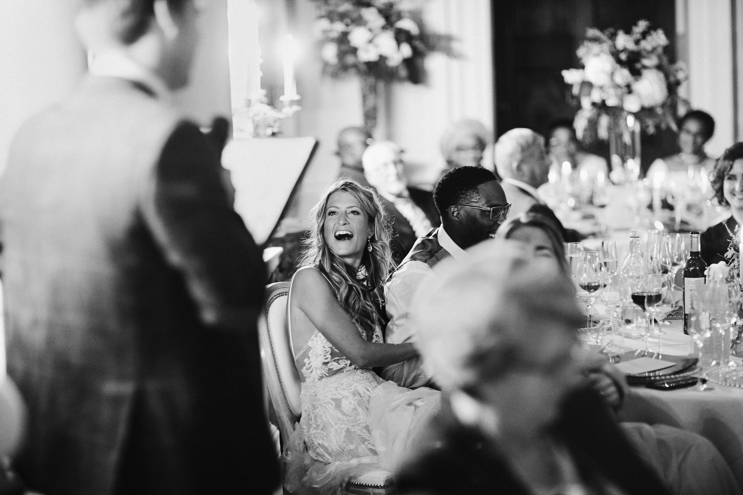 bride laughs at speeches during wedding dinner