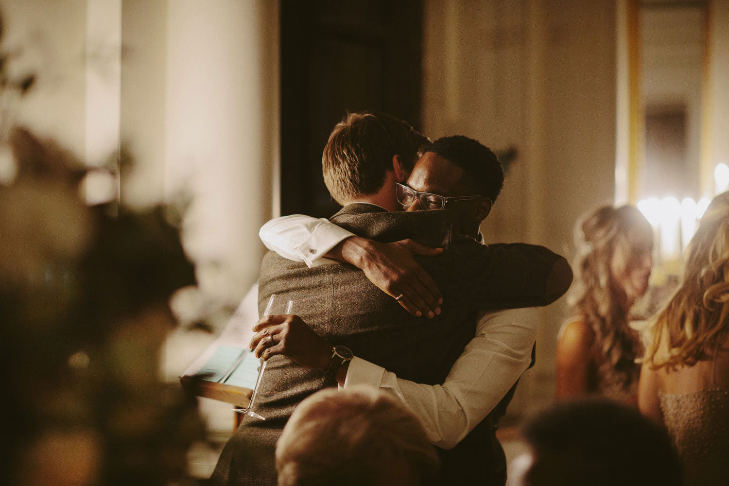 groom hugs best man during dinner