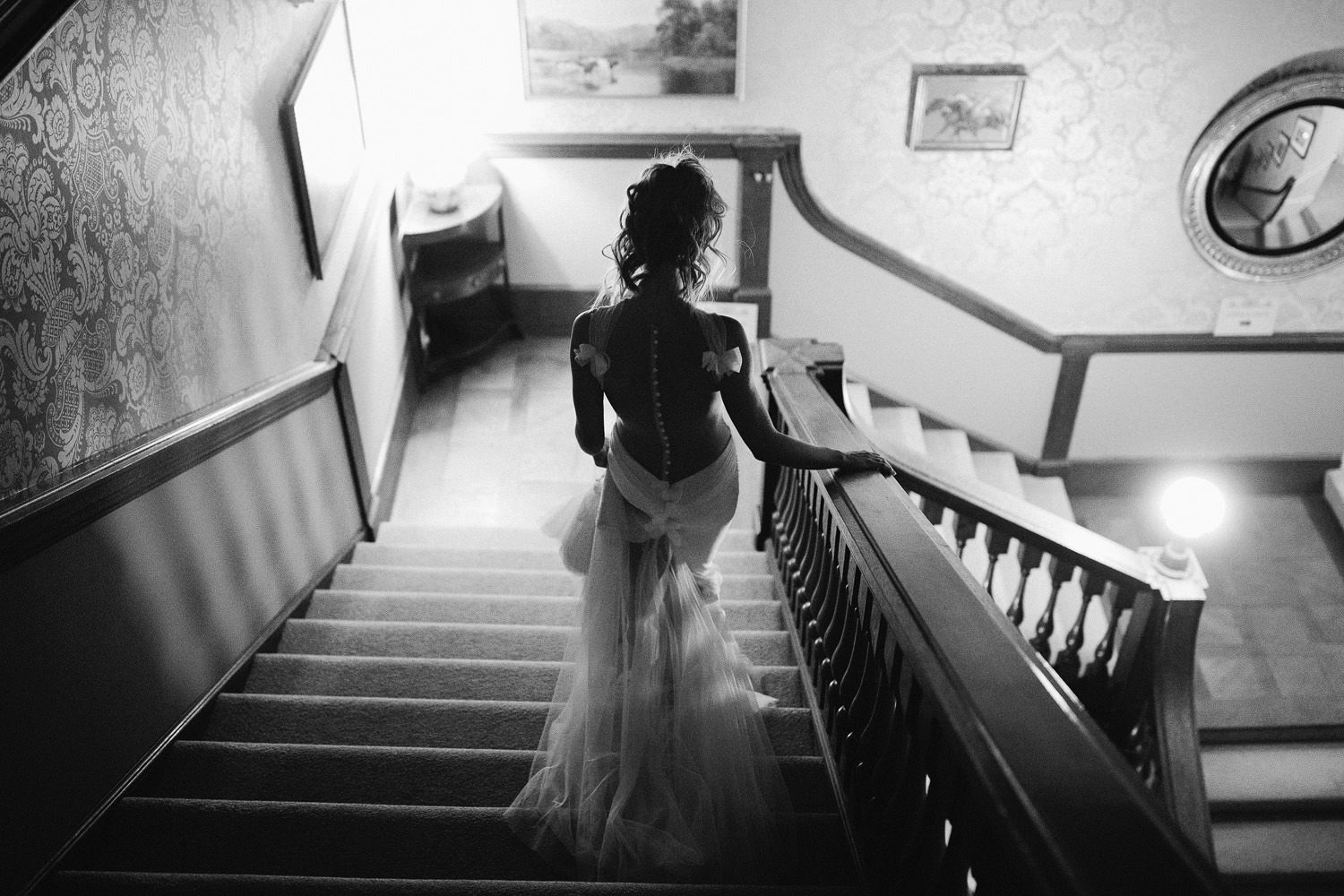 bride walks down steps in the evening with backless dress