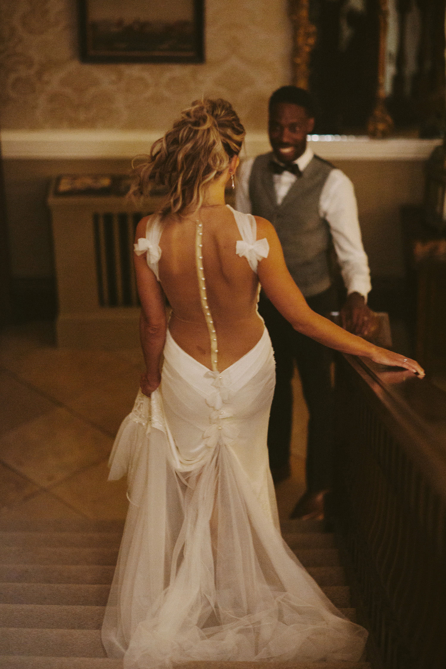 groom watches bride walk down steps towards him in evening dress