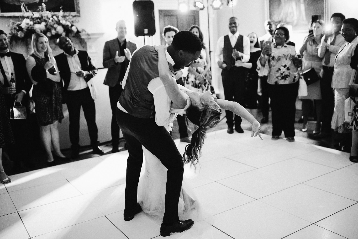 groom bends bride backwards during first dance at wedding