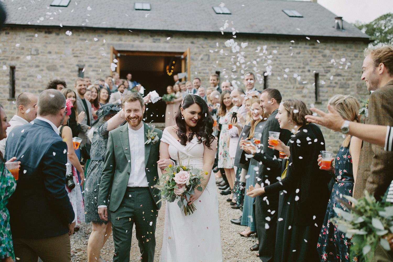 bride and groom walk out of barn at Cartmel with guests throwing confetti