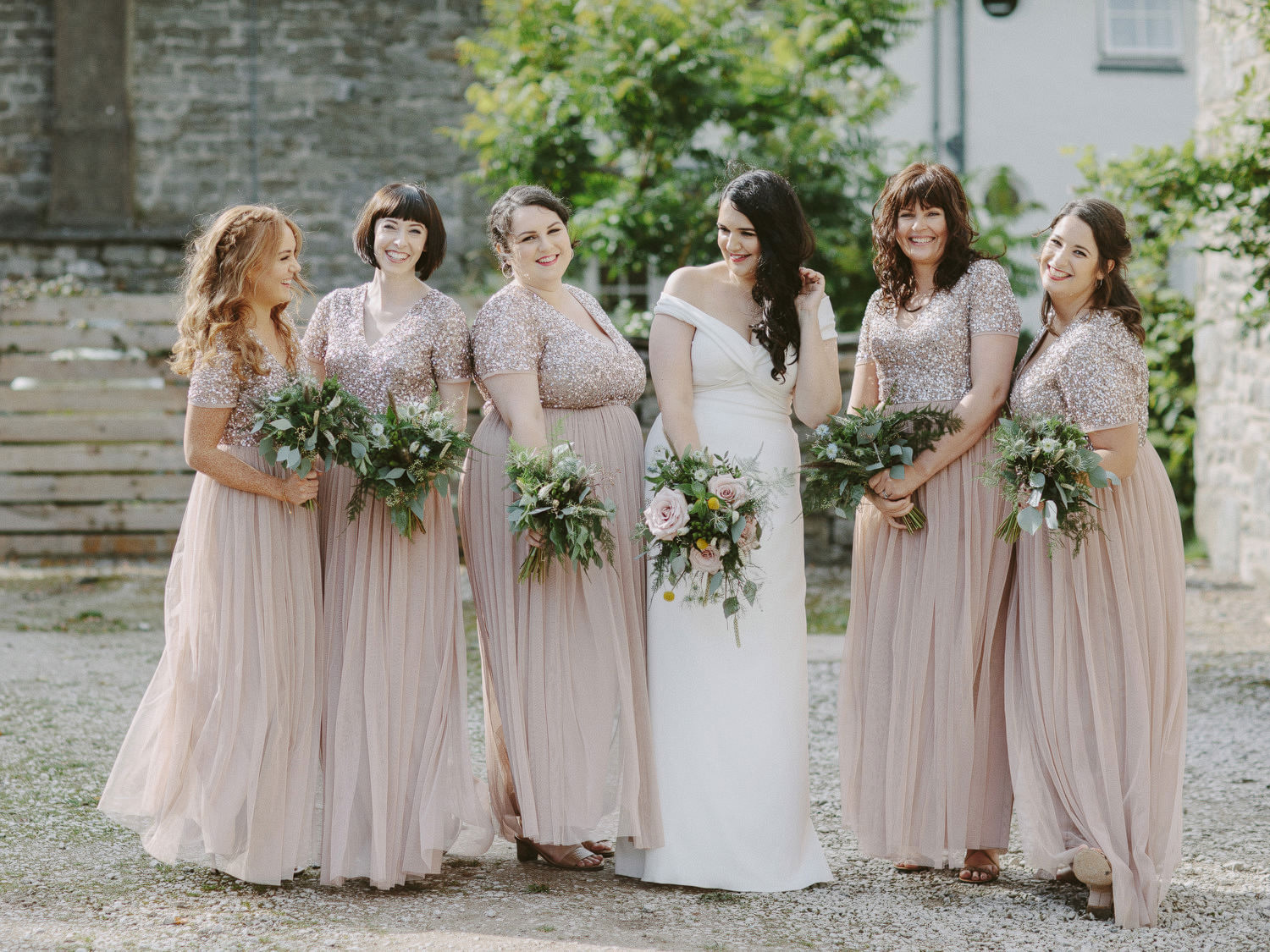 bridesmaids with sequin tops and bride laugh outside holding green and white bouquets