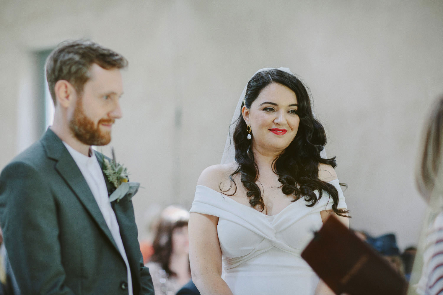 bride and groom smile during wedding ceremony at Cartmel