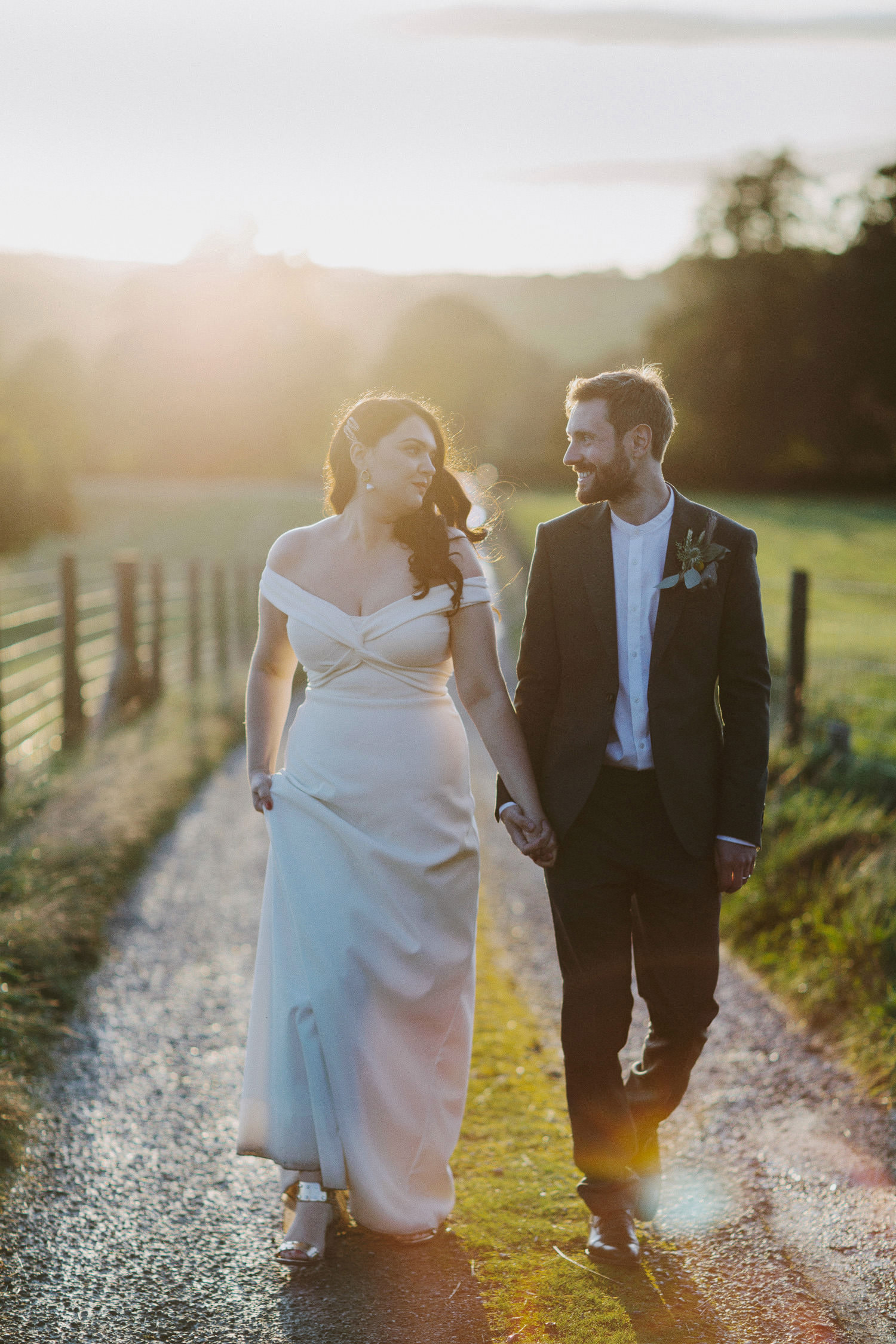bride and groom walk in sunset at caramel near lake windermere