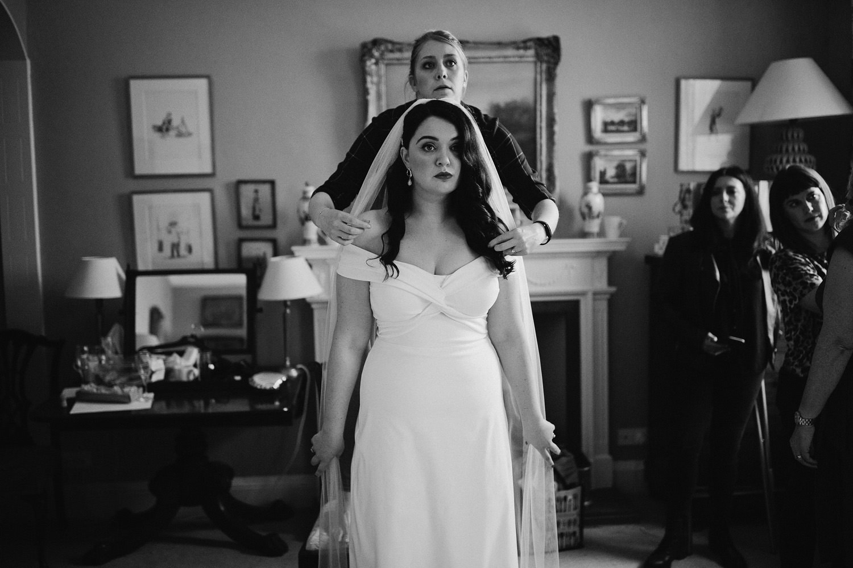 friend adjust veil while bride faces the mirror