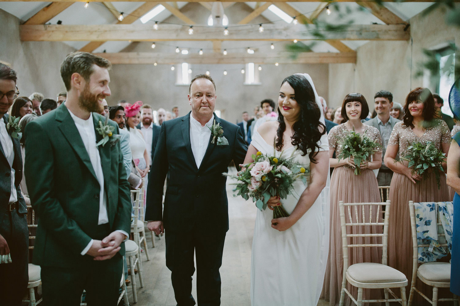 father walks with bride to front of ceremony while groom smiles