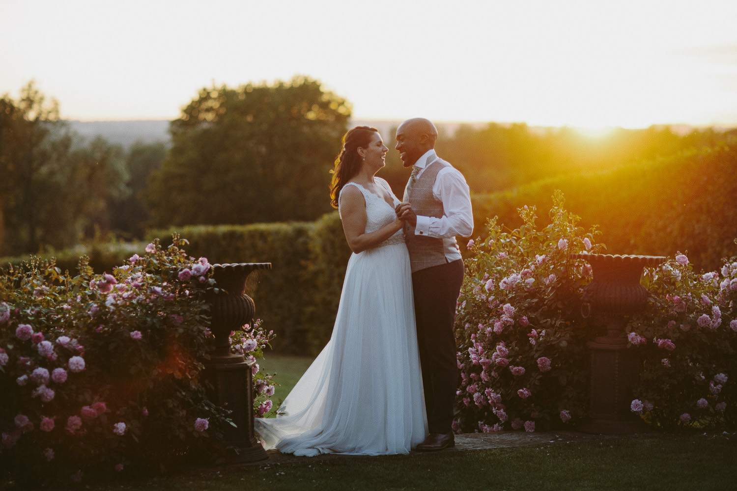 bride and groom stand holding hands in the sunset at Merriscourt barn