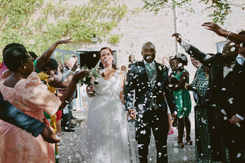 wedding couple walk through confetti outside Merriscourt barn