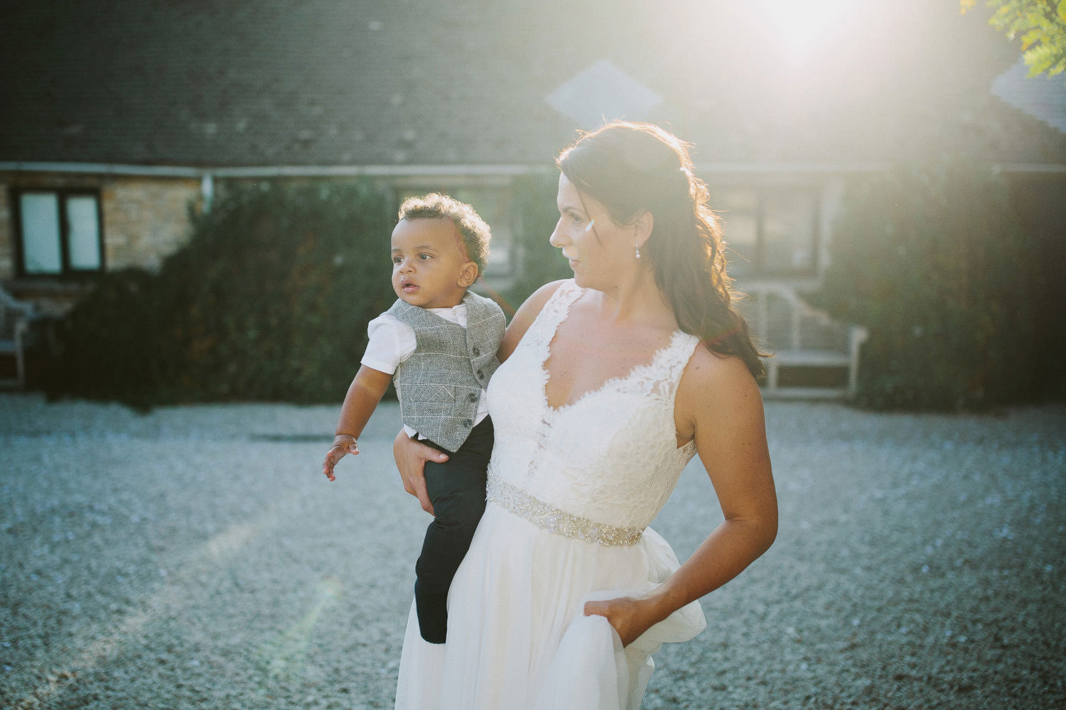 bride holds young boy on her hip