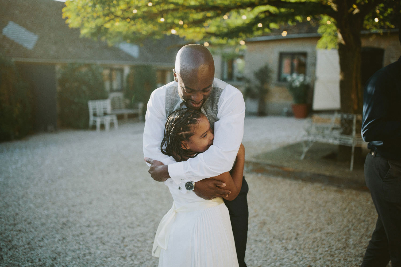groom hugs young bridesmaid