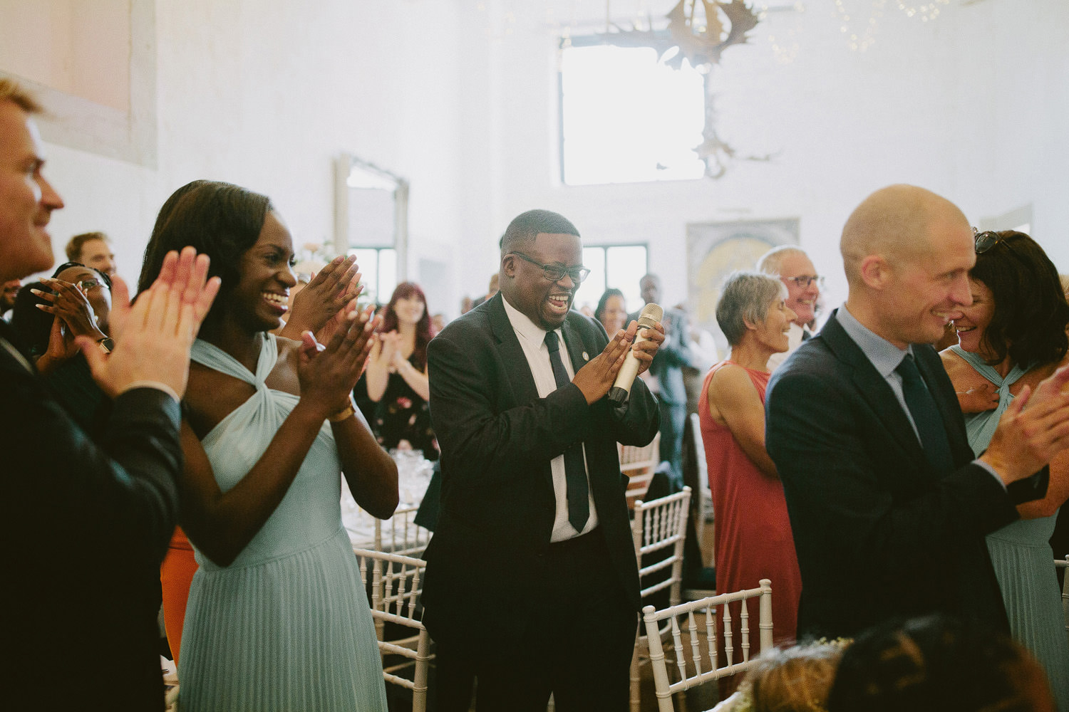 wedding guests stand clapping in white barn