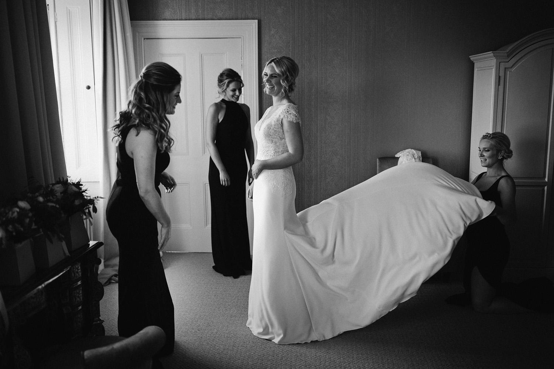 bridesmaids in black help bride get ready